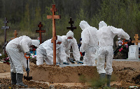 Grave diggers wearing protective gear during burial of suspected COVID-19 victim at Saint Petersburg