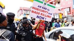 A member of #RevolutionNow and policemen during a protest against bad governance and insecurity in t